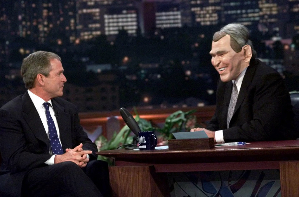 """. Talk show host Jay Leno, right, wears a Texas Gov. George W. Bush mask while interviewing the Republican presidential candidate during the taping of \""""The Tonight Show with Jay Leno,\"""" Monday, Oct. 30, 2000, in Burbank, Calif. (AP Photo/Eric Gay)"""