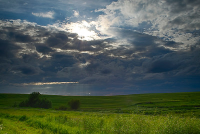 Cloudy day with a little sun shining over green fields