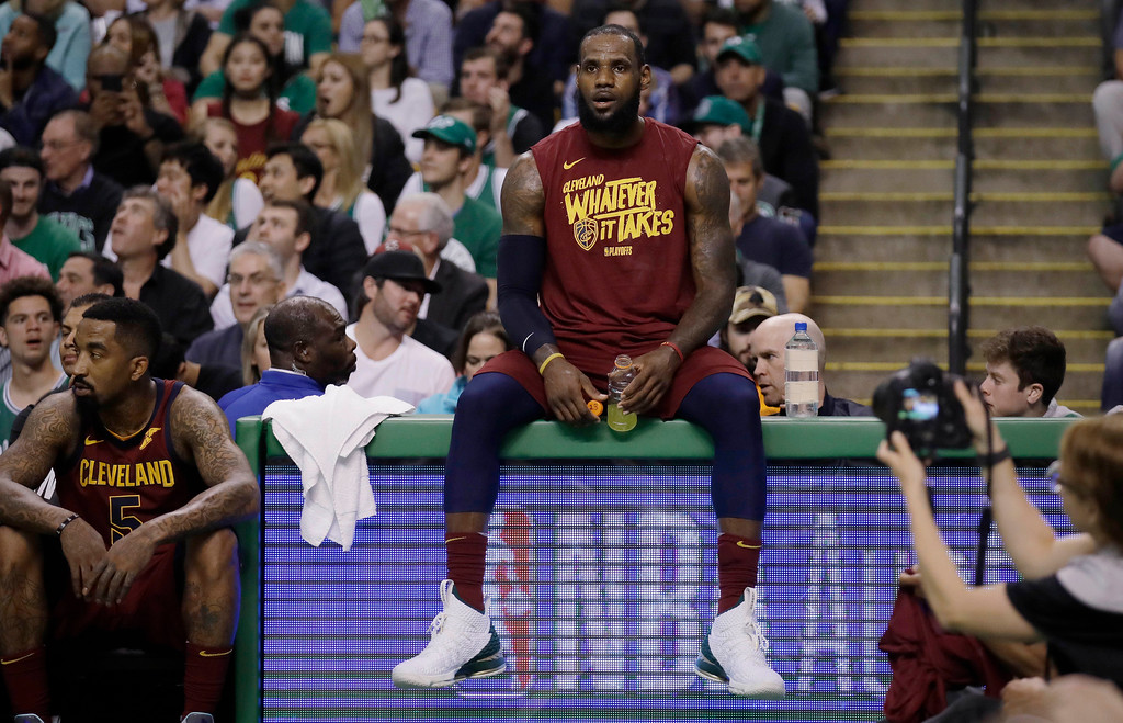 . Cleveland Cavaliers forward LeBron James sits on the scorer\'s table during a timeout in the first half in Game 2 of the team\'s NBA basketball Eastern Conference finals against the Boston Celtics, Tuesday, May 15, 2018, in Boston. At left is teammate JR Smith. (AP Photo/Charles Krupa)