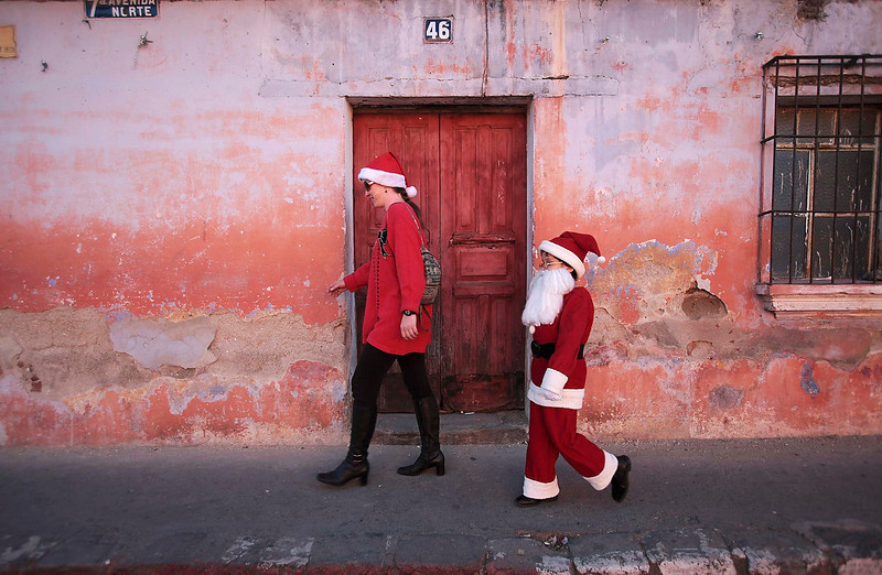 . Alexander, 9, dressed as Santa Claus, walks beside his mother in Antigua, about 26 from Guatemala City on December 23, 2012. REUTERS/William Gularte