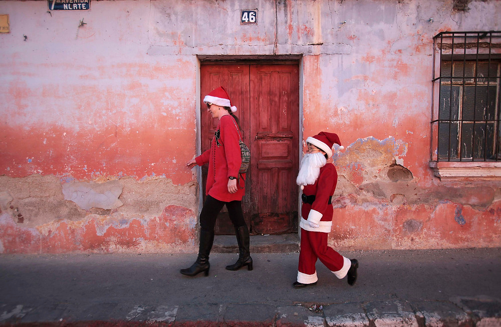 Description of . Alexander, 9, dressed as Santa Claus, walks beside his mother in Antigua, about 26 from Guatemala City on December 23, 2012. REUTERS/William Gularte