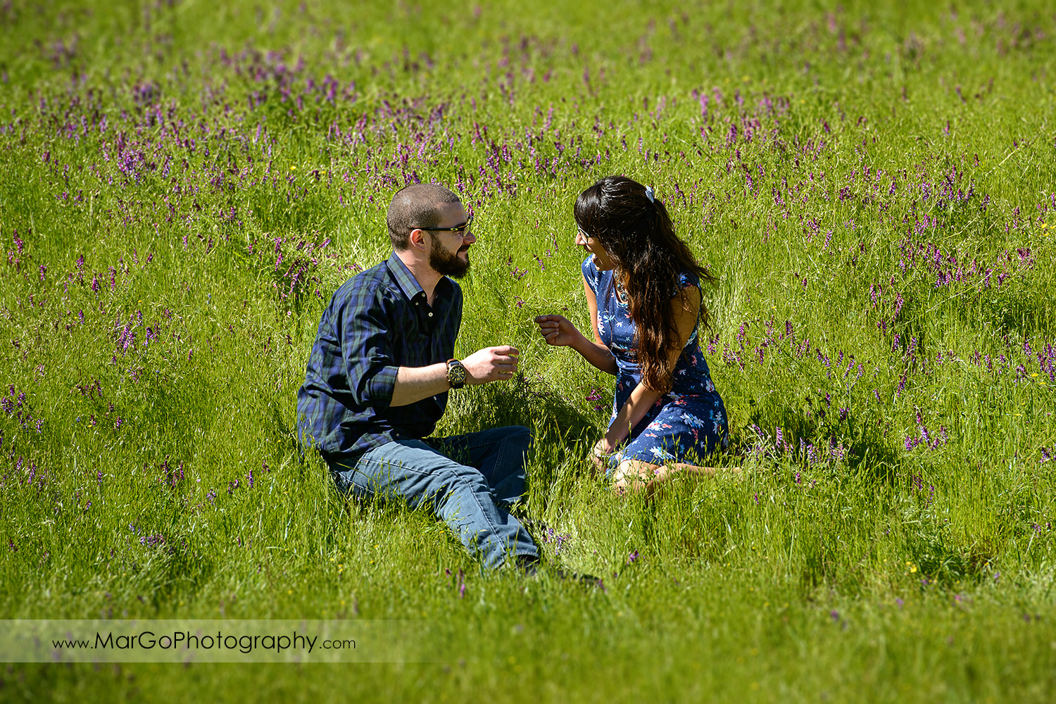 woman in blue dress and man in blue shirt sitting on the grass during engagement session at Sunol Regional Wilderness