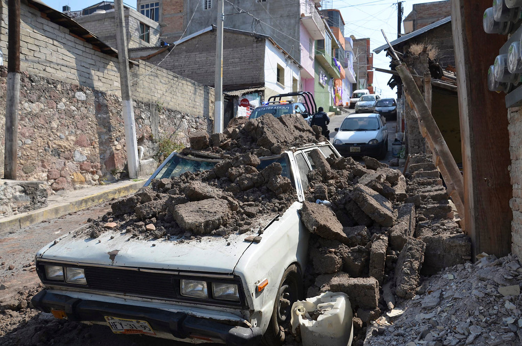 . A parked car suffered damage when a adobe wall collapsed on it after a strong earthquake shook Chilpancingo, Mexico, Friday morning, April 18, 2014. A powerful magnitude-7.2 earthquake shook central and southern Mexico but there were no early reports of major damage or casualties. (AP Photo/Alejandrino Gonzalez)