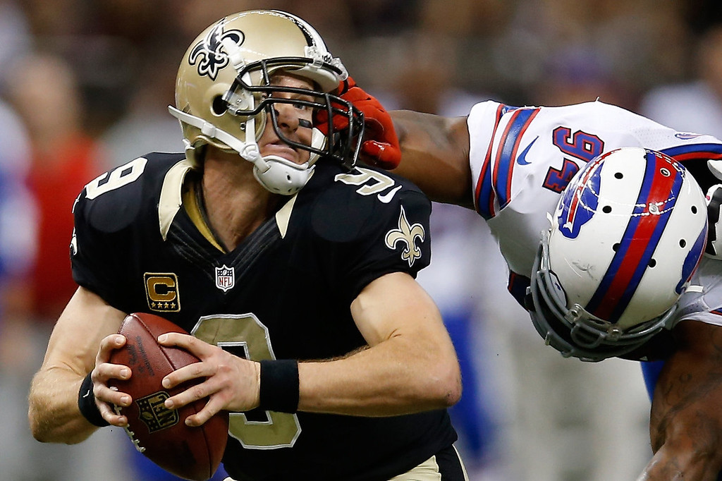 . Drew Brees #9 of the New Orleans Saints is pulled by the facemask by  Mario Williams #94 of the Buffalo Bills at Mercedes-Benz Superdome on October 27, 2013 in New Orleans, Louisiana.  (Photo by Chris Graythen/Getty Images)
