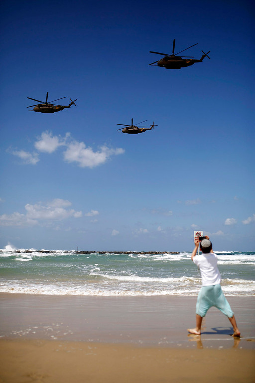 . A boy watches Israeli Air Force CH-53 helicopters fly over the Mediterranean Sea on a Tel Aviv beach, during an aerial show as part of celebrations for Israel\'s Independence Day, marking the 65th anniversary of the creation of the state, April 16, 2013. REUTERS/Amir Cohen
