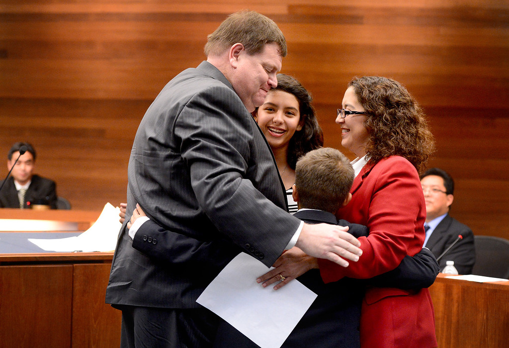 . Mike Spence, who won a West Covina council seat by two votes, is hugged by his wife Marielena and children Nathanael, 10, and Reagan, 13, after being sworn in in West Covina\'s council chambers Tuesday night, December 3, 2013. The city is holding a recount Wednesday for the council seat.  (Photo by Sarah Reingewirtz/Pasadena Star-News)