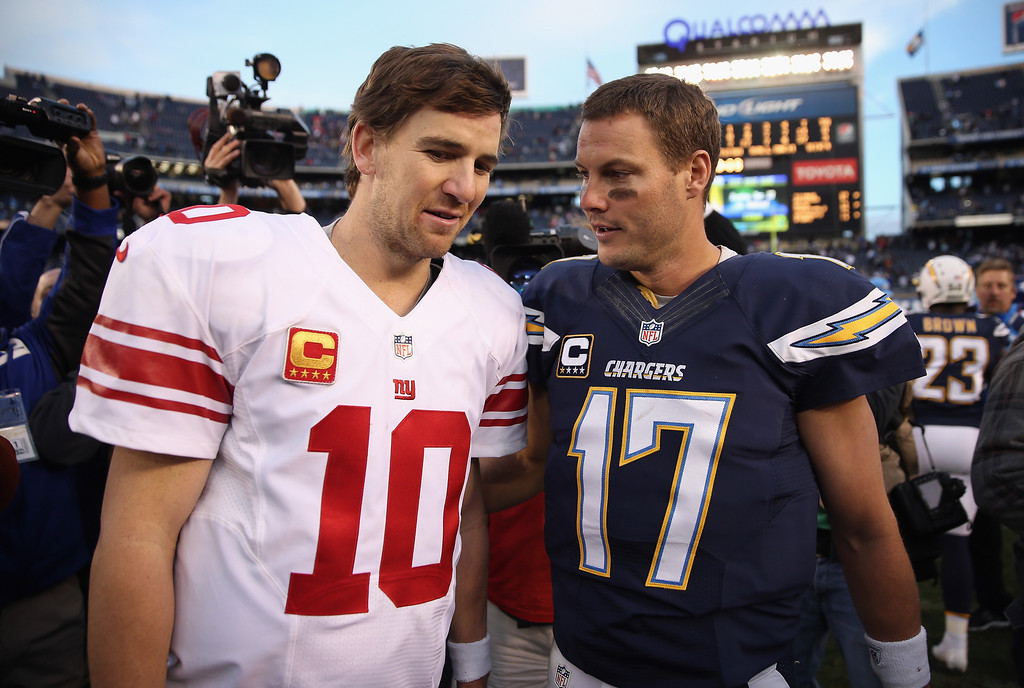 . SAN DIEGO, CA - DECEMBER 08:  Eli Manning #10 of the New York Giants and Philip Rivers #17 of the San Diego Chargers come together at the conclusion of the game at Qualcomm Stadium on December 8, 2013 in San Diego, California. The Chargers defeated the Giants 37-14. (Photo by Jeff Gross/Getty Images)