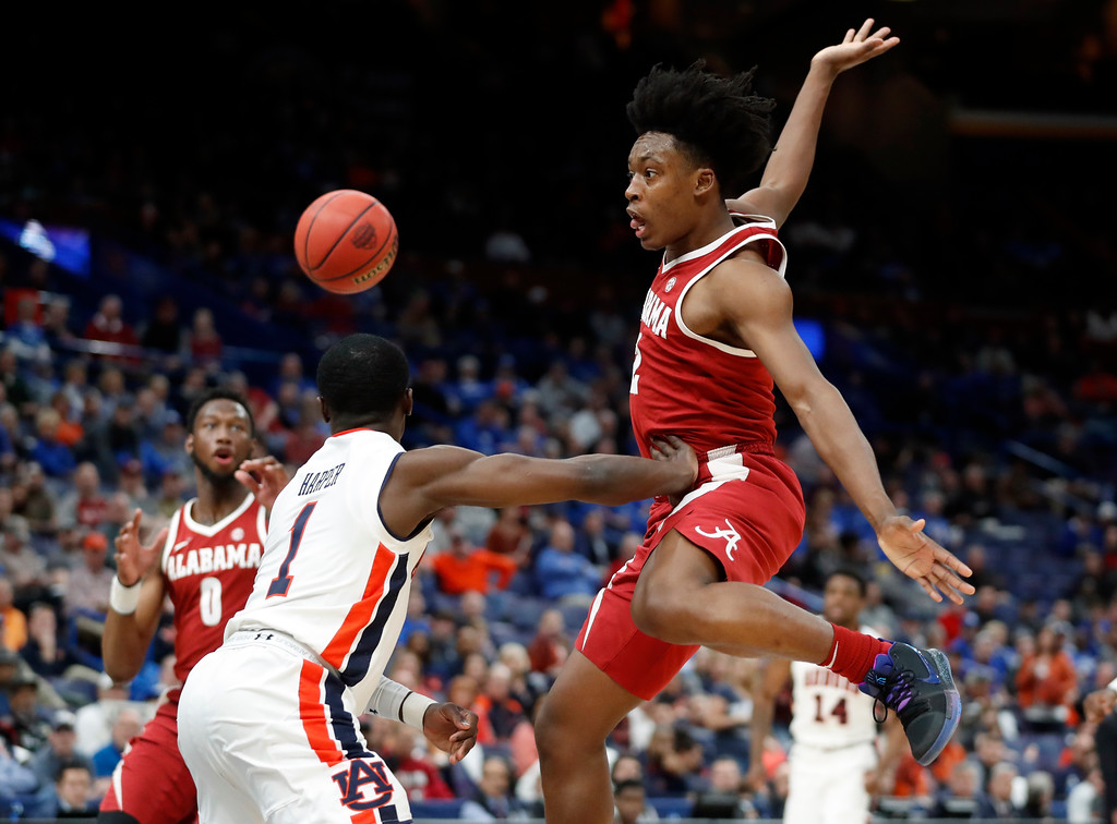 . Alabama\'s Collin Sexton, right, makes a no-look pass to teammate Donta Hall, left, around Auburn\'s Jared Harper, center, during the second half in an NCAA college basketball quarterfinal game at the Southeastern Conference tournament Friday, March 9, 2018, in St. Louis. Alabama won 81-63. (AP Photo/Jeff Roberson)