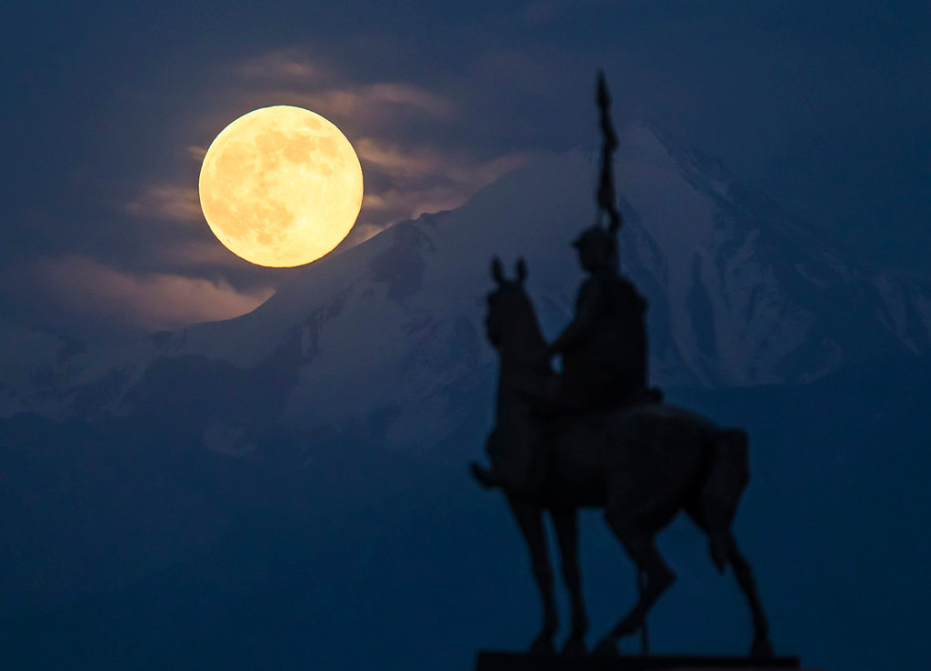 ". The largest full moon of 2013, a ""super moon\"" scientifically known as a \""perigee moon\"", rises over the Tien Shan mountains and the monument to 18th century military commander Nauryzbai Batyr near the town of Kaskelen, some 14 miles west of Almaty in Kazakhstan on June 23, 2013.  REUTERS/Shamil Zhumatov"