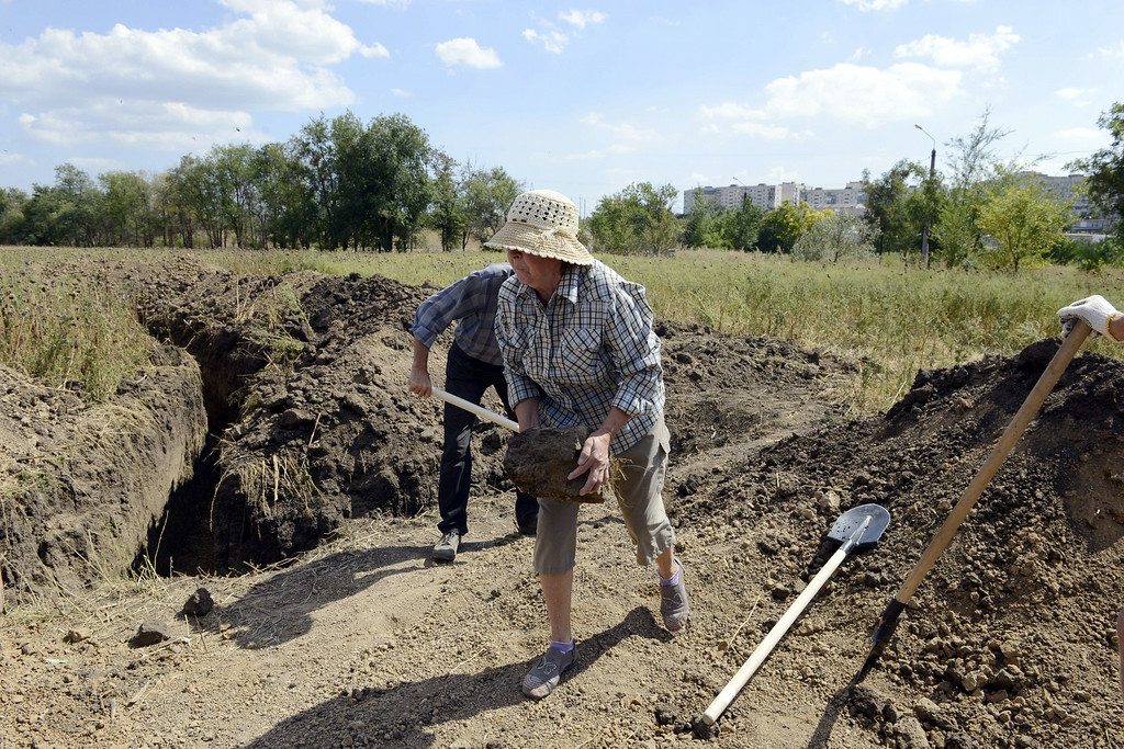 """. Residents of Mariupol dig trenches and make fortifications with sandbags as they assist Ukrainian troops in organising their defence on the outskirts of the southern Ukrainian city of Mariupol on August 29, 2014. NATO chief Anders Fogh Rasmussen urged Russia on August 29 to halt its \""""illegal\"""" military actions in Ukraine, accusing it of a \""""dangerous\"""" attempt to destabilise its western neighbour. The conflict raging in eastern Ukraine has killed nearly 2,600 people, the United Nations said on August 29, voicing concern about atrocities committed by armed groups and the increasing involvement of foreign fighters. Alexander KHUDOTEPLY/AFP/Getty Images"""