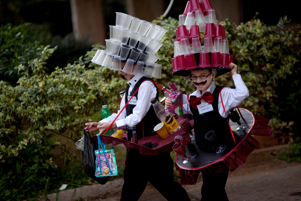 Description of . Moti and Elazar, 8, two Ultra Orthodox Jewish boys dressed in costumes walk during the Purim festival in the ultra-Orthodox town of Bnei Brak, Israel,Sunday, Feb. 24, 2013. The Jewish holiday of Purim commemorates the Jews\' salvation from genocide in ancient Persia, as recounted in the Book of Esther which is read in synagogues. Other customs include: sending food parcels and giving charity, dressing up in masks and costumes, eating a festive meal, and public celebration. (AP Photo/Ariel Schalit)