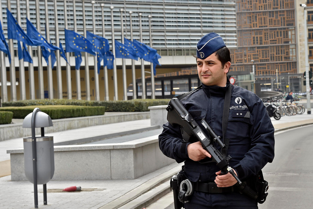 . Police patrol the EU commission building, after  a bomb exploded nearby, at the subway in Brussels, Belgium, Tuesday, March 22, 2016. Authorities locked down the Belgian capital on Tuesday after explosions rocked the Brussels airport and subway system, killing  a number of people and injuring many more. Belgium raised its terror alert to its highest level, diverting arriving planes and trains and ordering people to stay where they were. Airports across Europe tightened security. (AP Photo/Martin Meissner)