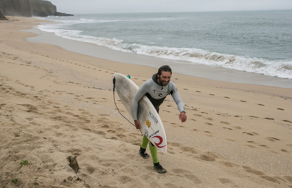 . Surfer Joao Demacedo walks down the beach after surfing at  Martin\'s Beach in Half Moon Bay, Calif., on Thursday, March 14, 2013. Martin\'s Beach was closed to public access in 2008 when the property was purchased by venture capitalist Vinod Khosla.