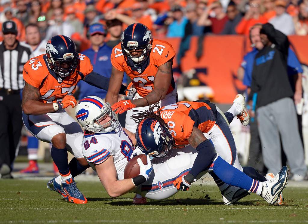 . DENVER, CO - DECEMBER 07: David Bruton (30) of the Denver Broncos takes down Scott Chandler (84) of the Buffalo Bills during the first quarter.  The Denver Broncos played the Buffalo Bills at Sports Authority Field at Mile High in Denver, Colo. on December 7, 2014. (Photo by Joe Amon/The Denver Post)