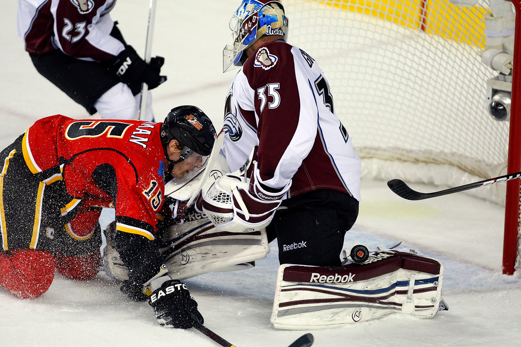 . Colorado Avalanche goalie Jean-Sebastien Giguere, right, looks for the puck as it bounces off his pad, while Calgary Flames\' Tim Jackman crashes into him during the first period of an NHL hockey game Thursday, Jan. 31, 2013, in Calgary, Alberta. (AP photo/The Canadian Press, Jeff McIntosh)