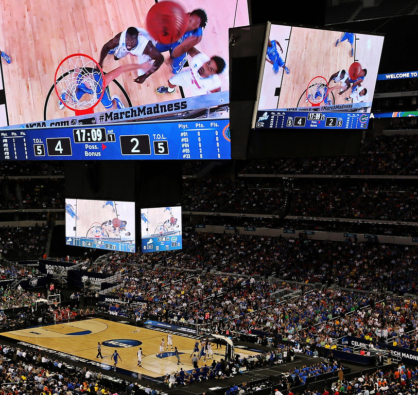 . Florida and Florida Gulf Coast  are seen through overhead screens during the first half of a regional semifinal game in the NCAA college basketball tournament, Friday, March 29, 2013, in Arlington, Texas. (AP Photo/Tim Donnelly)