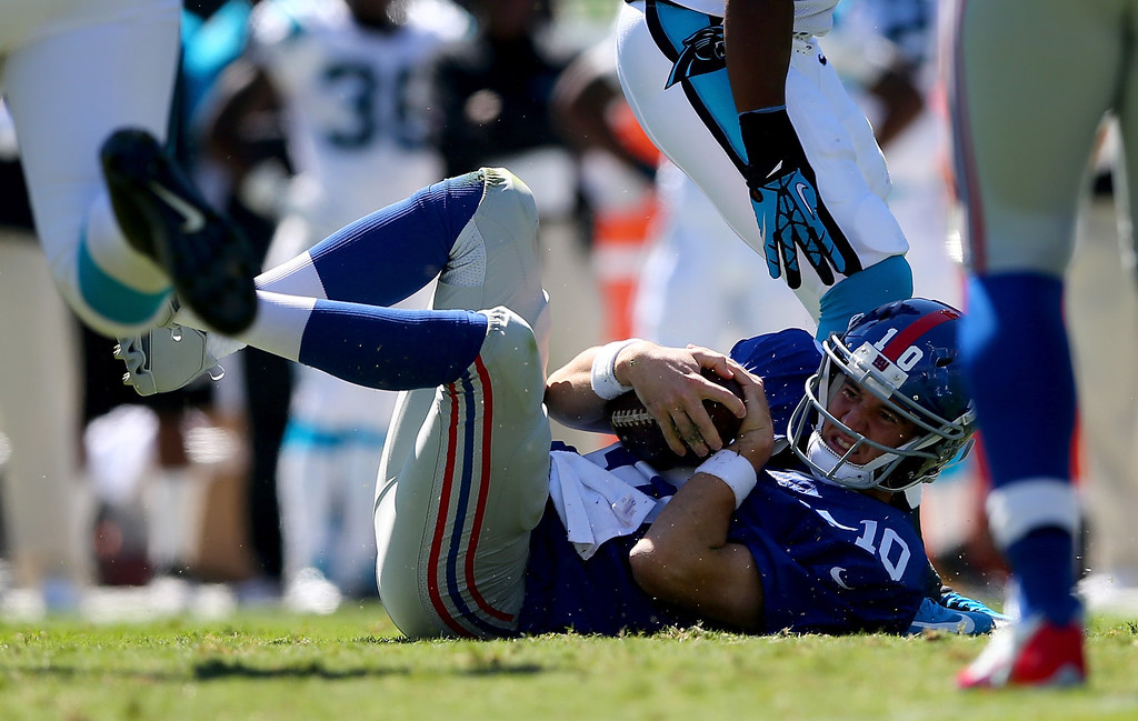 . Eli Manning #10 of the New York Giants is knocked to the ground during their game against the Carolina Panthers at Bank of America Stadium on September 22, 2013 in Charlotte, North Carolina.  (Photo by Streeter Lecka/Getty Images)