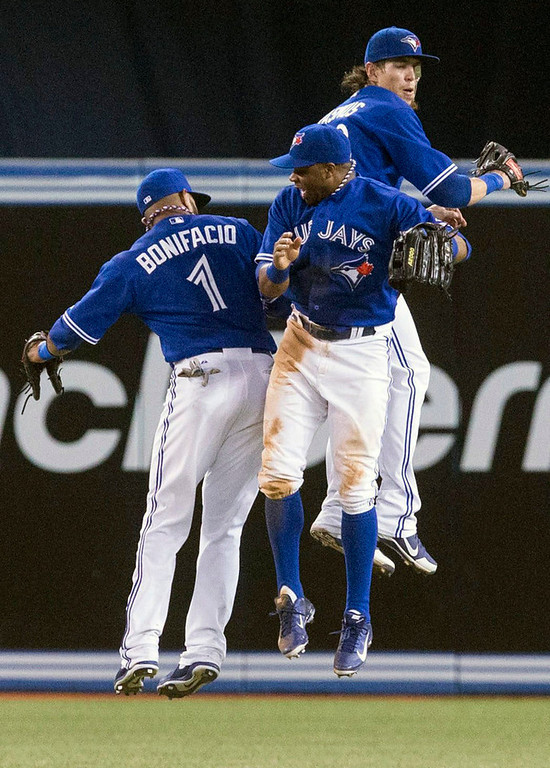. Blue Jays outfielders, from left, Emilio Bonifacio, Rajai Davis and Colby Rasmus celebrate their 11-5 win over the Twins. (AP Photo/The Canadian Press, Chris Young)