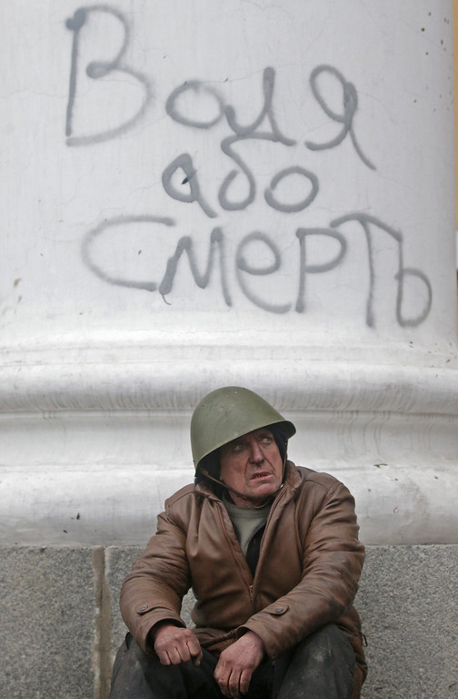 . Radical opposition fighter rests on a column with a graffiti that reads \'freedom or death\' during clashes with riot police on the Independence square in Kiev, Ukraine, 20 February 2014.  EPA/MAXIM SHIPENKOV