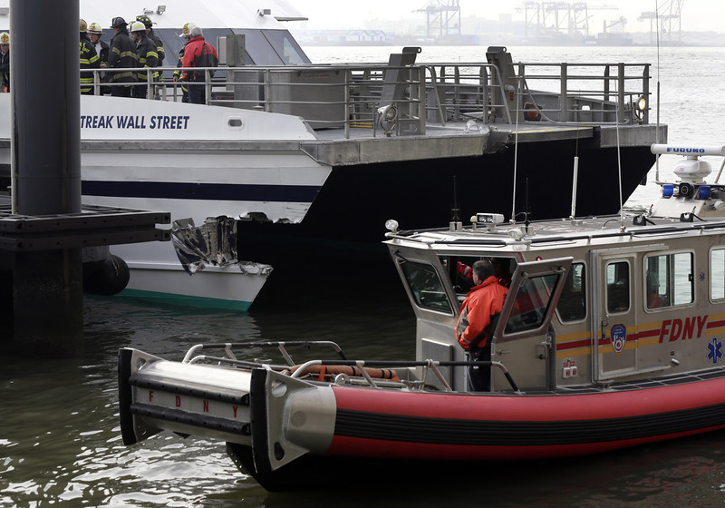 . New York City firefighters walk the deck of the Seastreak Wall Street ferry in New York,  Wednesday, Jan. 9, 2013. The ferry from Atlantic Highlands, N.J., banged into the mooring as it arrived at South Street in lower Manhattan during morning rush hour, injuring as many as 50 people, at least one critically, officials said.(AP Photo/Richard Drew)