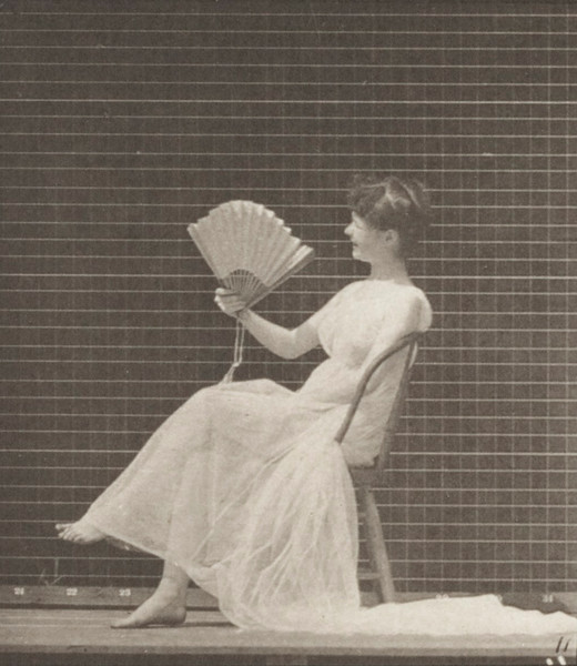 Semi-nude woman placing chair, sitting and flirting a fan