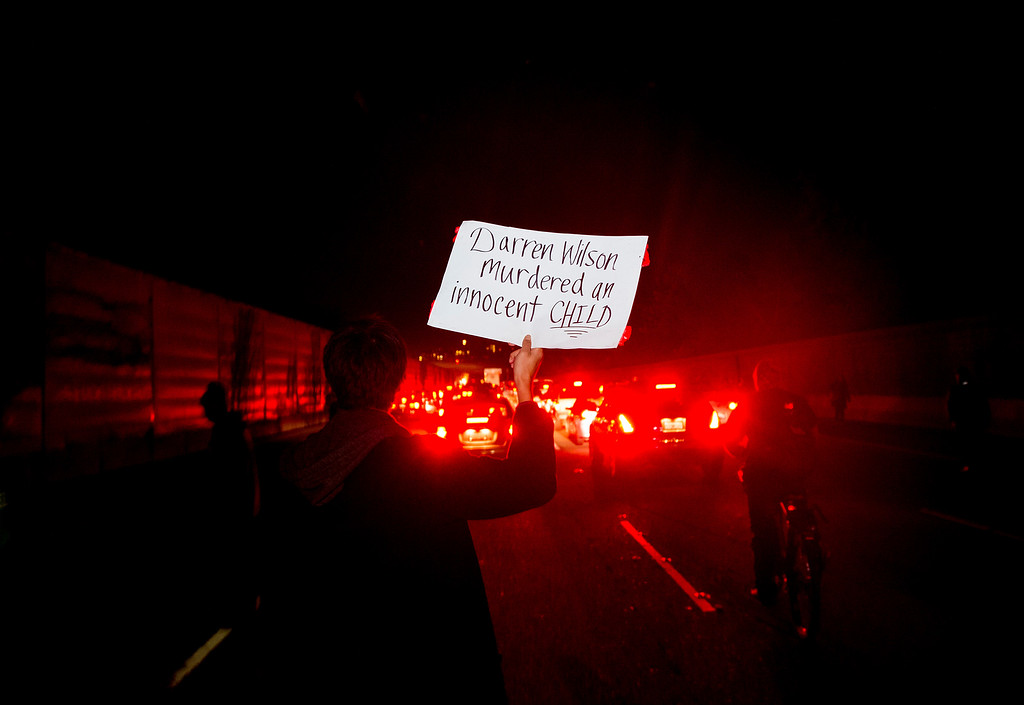 . Dante Kaleo holds a protest sign while marching on Interstate 580 in Oakland, Calif., on Monday, Nov. 24, 2014, after the announcement of the grand jury decision not to indict Ferguson police officer Darren Wilson in the fatal shooting of Michael Brown, an unarmed 18-year-old. Several thousand protesters marched through Oakland with some shutting down freeways multiple times, burning refuse and breaking windows on a news van. (AP Photo/Noah Berger)