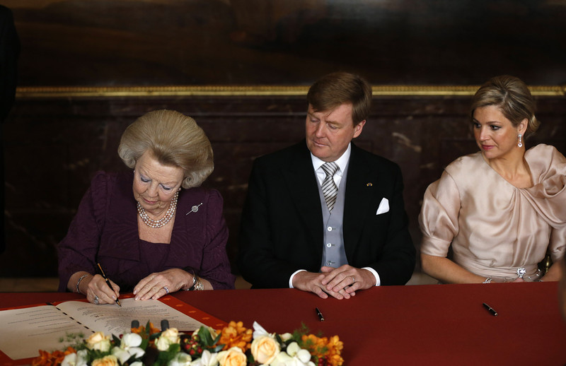 . Queen Beatrix of the Netherlands (L) signs her name to the Act of Abdication as her son Prince Willem-Alexander of the Netherlands and his wife Princess Maxima of the Netherlands (R) watches during the abdication ceremony in the Moseszaal at the Royal Palace on April 30, 2013 in Amsterdam. Queen Beatrix of the Netherlands is abdicating the throne after a 33 year reign and hands the throne to her son Prince Willem-Alexander who will be sworn in later at the Nieuwe Kerk ahead of a joint session of parliament. (Photo by Bart Maat - Pool/Getty Images)