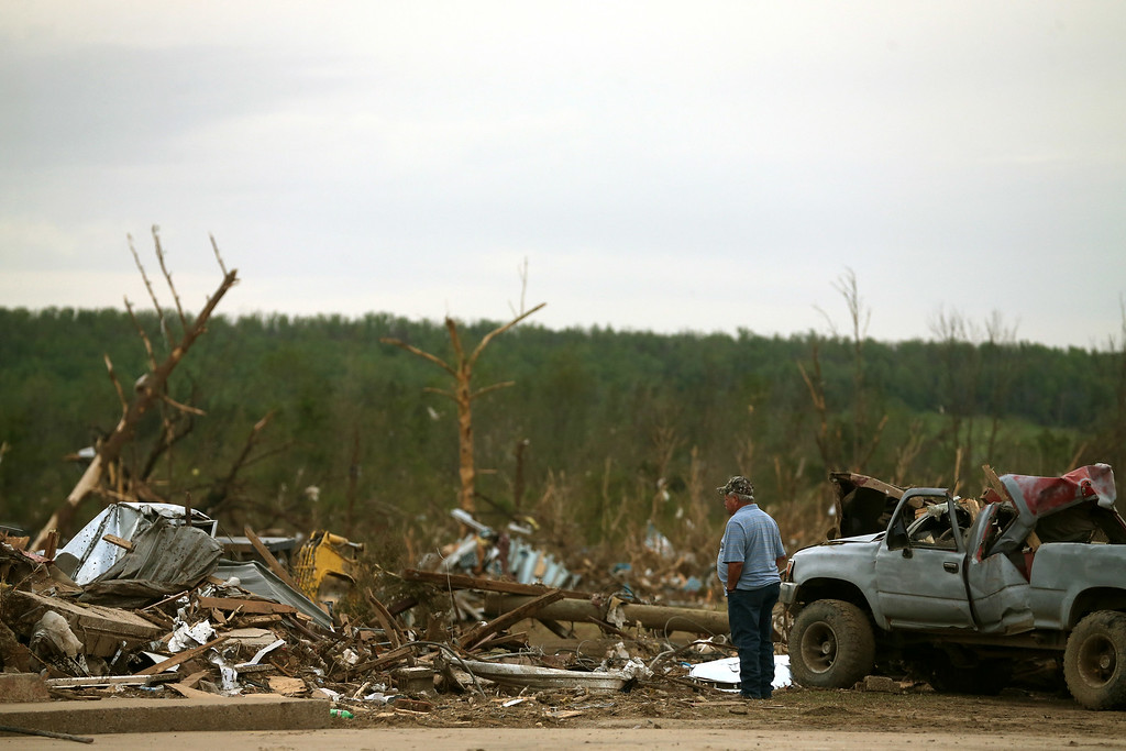 . A passerby stops to look at damage caused by a tornado on Sunday evening, on April 29, 2014 in Vilonia, Arkansas. After deadly tornadoes ripped through the region leaving more than a dozen dead, Mississippi, Arkansas, Texas, Louisiana and Tennessee are all under watch as multiple storms are expected over the next few days.  (Photo by Mark Wilson/Getty Images)