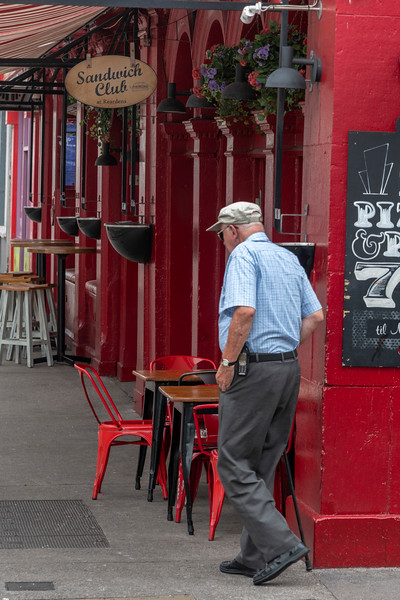 Senior man walking past a caf�, City of Cork, County Cork, Ireland
