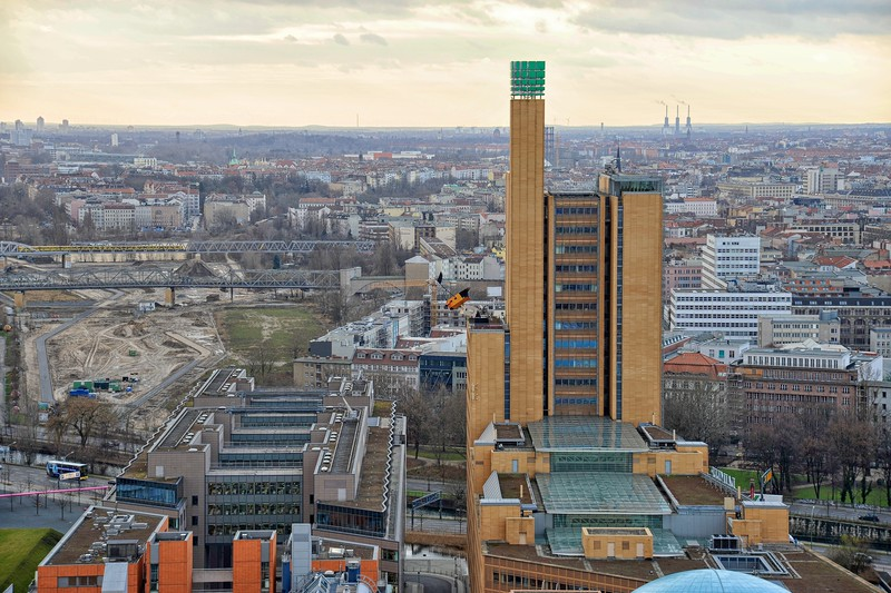 Looking south to the Debis Tower from the Kollhof Building, Potsdamer Platz. The three towers (102 metres tall)  of the Wilmersdorf Power Station can be seen to the right of the Debis Tower, 5 miles to the southwest.