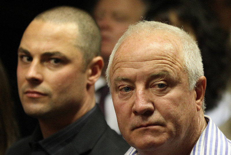 . Olympic athlete Oscar Pistorius\' father Henke Pistorius, right, with his son Carl watch as Oscar Pistorius walks in during his bail hearing at the magistrate court in Pretoria, South Africa, Friday, Feb. 22, 2013. (AP Photo/Themba Hadebe)