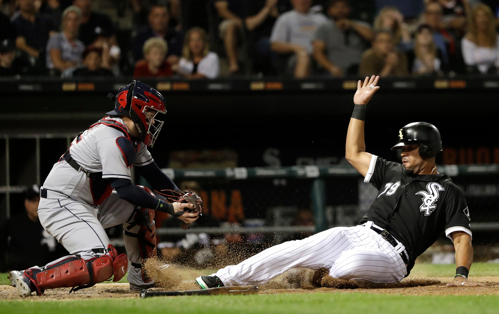 . Chicago White Sox\'s Jose Abreu, right, avoids the tag of Cleveland Indians catcher Roberto Perez, scoring on a single by Kevan Smith during the sixth inning of a baseball game Wednesday, June 13, 2018, in Chicago. (AP Photo/Charles Rex Arbogast)