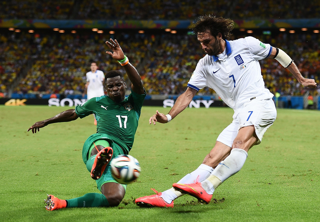 . Serge Aurier of the Ivory Coast challenges Giorgos Samaras of Greece during the 2014 FIFA World Cup Brazil Group C match between Greece and the Ivory Coast at Castelao on June 24, 2014 in Fortaleza, Brazil.  (Photo by Laurence Griffiths/Getty Images)