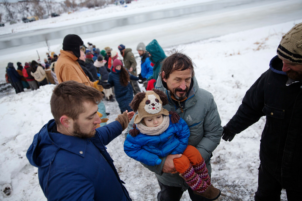 . Scott Levy, right, carries Spain Carlson, 3, of Fort Hall, Idaho, after releasing tobacco at the edge of the Cannonball river during a Native American water ceremony at the Oceti Sakowin camp where people have gathered to protest the Dakota Access oil pipeline in Cannon Ball, N.D., Friday, Dec. 2, 2016. According to Native American beliefs, tobacco is used to open a barrier between the physical and the spiritual worlds. (AP Photo/David Goldman)