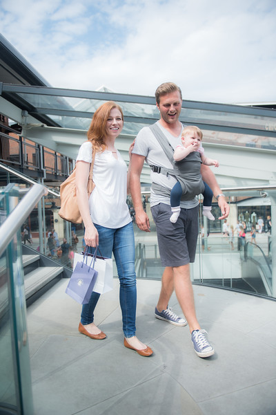 Izmi_Baby_Carrier_Mid_Grey_Lifestyle_Front_Facing_Carry_Mum_And_Dad_Shopping_Walking.jpg
