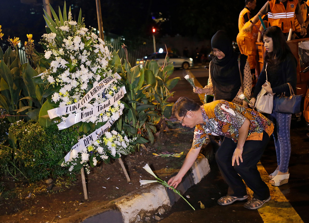 """. Indonesians lay flowers near the police post where an attack took place in Jakarta, Indonesia Thursday, Jan. 14, 2016. Attackers set off bombs and exchanged gunfire outside the cafe in Indonesia\'s capital in a brazen assault Thursday that police said \""""imitated\"""" the recent Paris attacks. (AP Photo/Dita Alangkara)"""