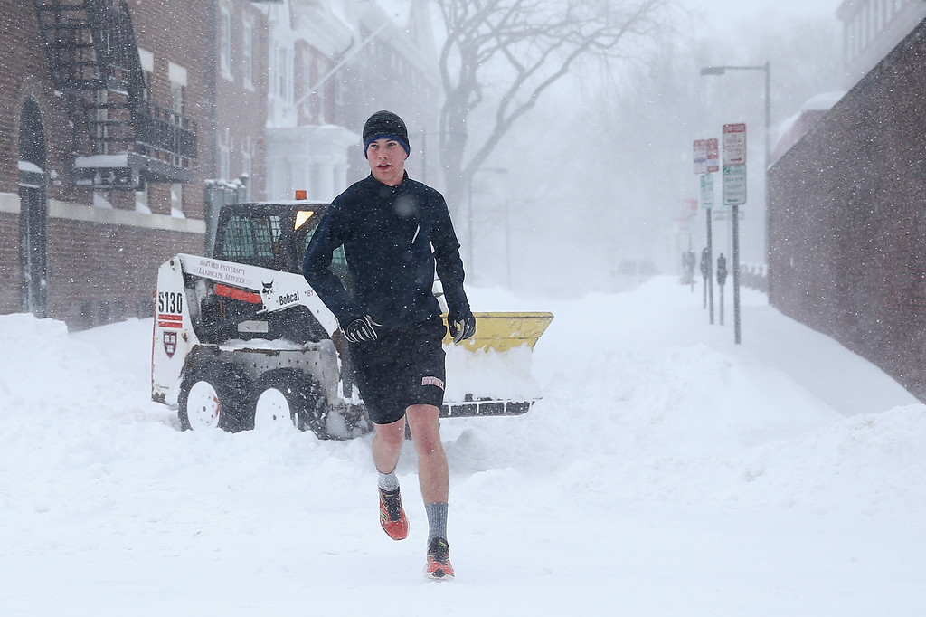 . A jogger runs through Cambridge as snow is cleared on January 27, 2015 in Cambridge, Massachusetts. Boston, and much of the Northeast, is being hit with heavy snow from Winter Storm Juno.  (Photo by Maddie Meyer/Getty Images)