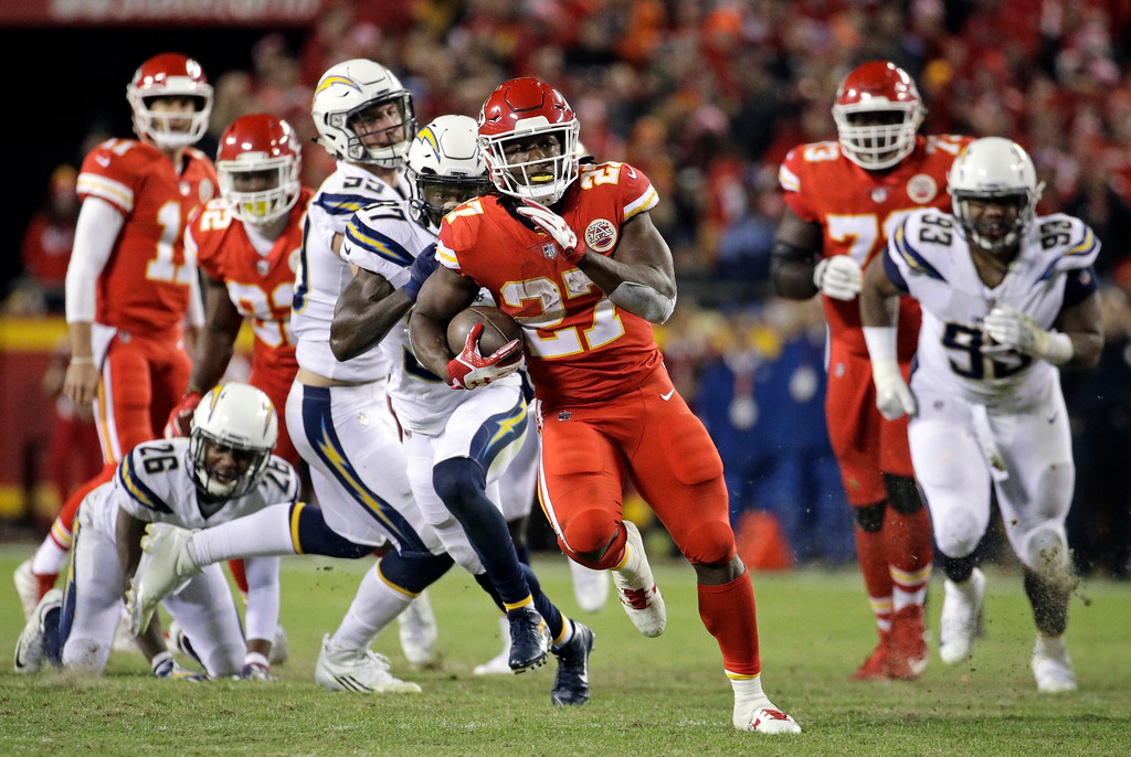 . Kansas City Chiefs running back Kareem Hunt (27) runs ahead of Los Angeles Chargers safety Jahleel Addae (37) during the second half of an NFL football game in Kansas City, Mo., Saturday, Dec. 16, 2017. (AP Photo/Charlie Riedel)