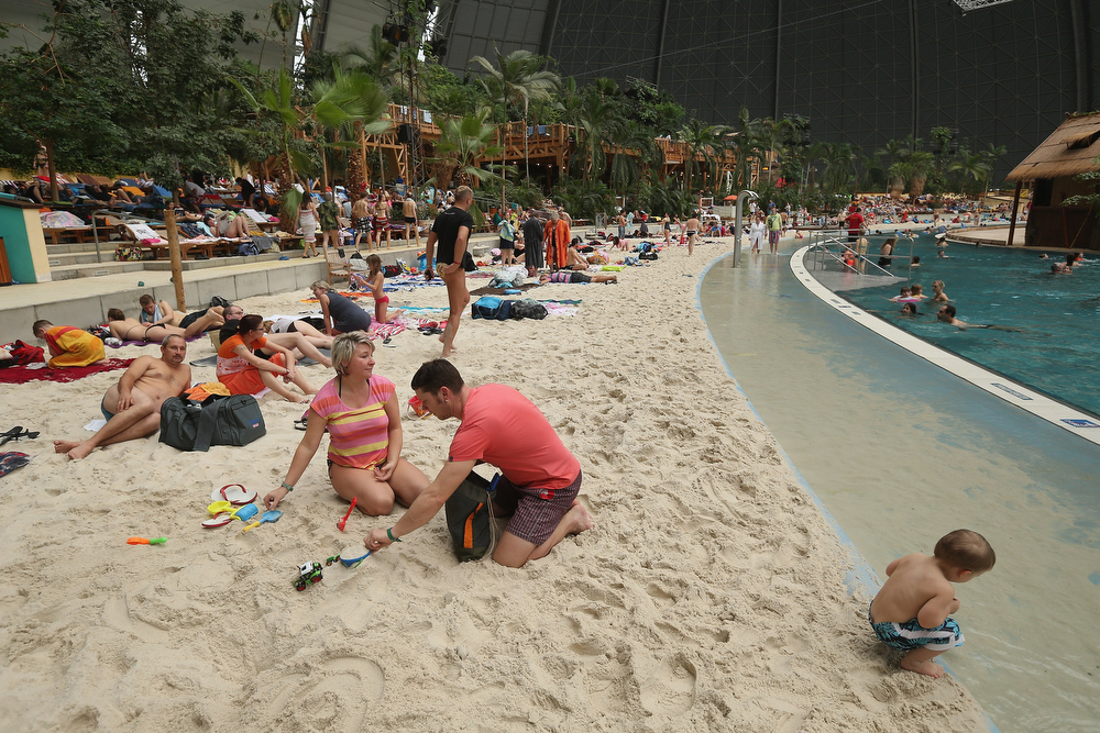 "Description of . A couple from the east German city of Chemnitz lounge with their son at the ""South Sea\"" beach at the Tropical Islands indoor resort on February 15, 2013 in Krausnick, Germany. Located on the site of a former Soviet military air base, the resort occupies a hangar built originally to house airships designed to haul long-distance cargo. Tropical Islands opened to the public in 2004 and offers visitors a tropical getaway complete with exotic flora and fauna, a beach, lagoon, restaurants, water slide, evening shows, sauna, adventure park and overnights stays ranging from rudimentary to luxury. The hangar, which is 360 metres long, 210 metres wide and 107 metres high, is tall enough to enclose the Statue of Liberty.  (Photo by Sean Gallup/Getty Images)"