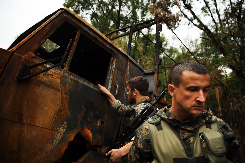 . ALOVAISK, UKRAINE - SEPTEMBER 10: Separatists fighters stand beside a Ukrainian military truck which was destroyed during recent fighting on September 10, 2014 in Alovaisk, Ukraine.  (Photo by Spencer Platt/Getty Images)