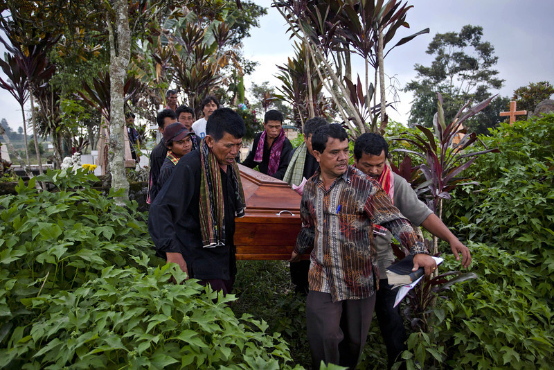 . Relatives carry a coffin during the burial of a victim that was killed after being hit by pyroclastic smoke from the eruption of Mount Sinabung on February 02, 2014 in Suka village, Karo District, North Sumatra, Indonesia. The number of displaced people has increased to around 30,000 in Western Indonesia as Mount Sinabung continues to spew ash and smoke after a series of several eruptions since September. At least 15 people have been killed in a eruption of Mount Sinabung, as residents returned to their local homes after they were told by authorities that activity was decreasing. (Photo by Ulet Ifansasti/Getty Images)