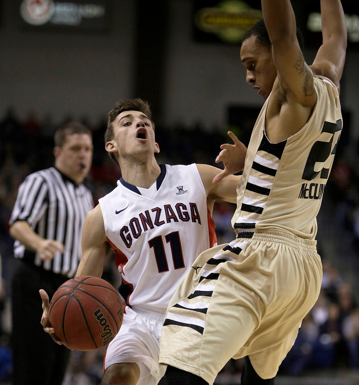 . Gonzaga�s David Stockton (11) attempts to dribble around Oakland\'s Tommy McCune (23) during an NCAA basketball game, in Spokane, Wash., on Sunday, Nov. 17, 2013. (AP Photo/Young Kwak)