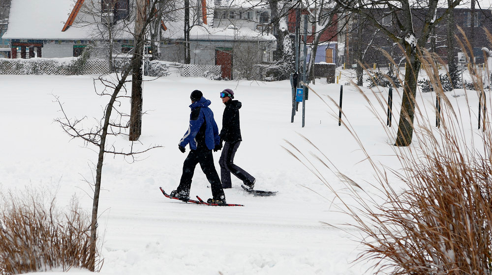 Description of . Jay Kotecha, left, and Erin Madar use snow shoes to walk on South Dunn near Kirkwood, Wednesday, Dec. 26, 2012 in Bloomington, Ind.  Madar said she has snow shoes because she used to live in Denver, Colorado. (AP Photo/Bloomington Herald-Times, Jeremy Hogan)