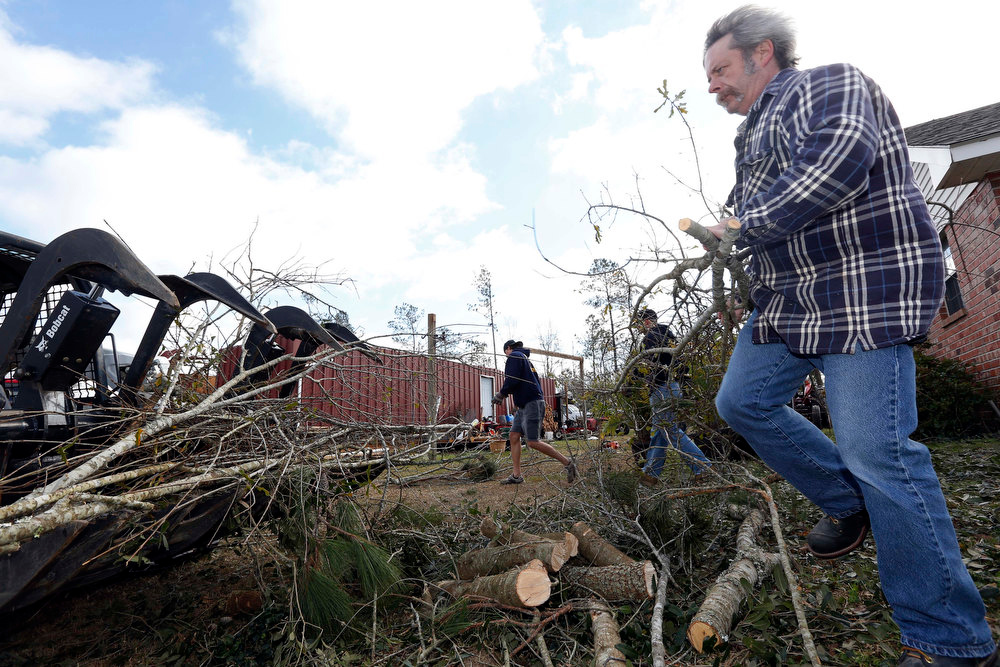Description of . Barry Caruso, a New Orleans fire fighter, hauls a downed branch to a debris pile at the home of his colleague Daryl Keene, in McNeill, Miss., Wednesday, Dec. 26, 2012. Keene's home sustained Christmas day storm damage destroying his barn, part of his roof, fencing and most of the oak trees on the property. More than 25 people were injured and at least 70 homes were damaged in Mississippi by the severe storms that pushed across the South on Christmas Day, authorities said Wednesday. Damages have been reported in 10 counties and officials continue to assess the situation. (AP Photo/Rogelio V. Solis)