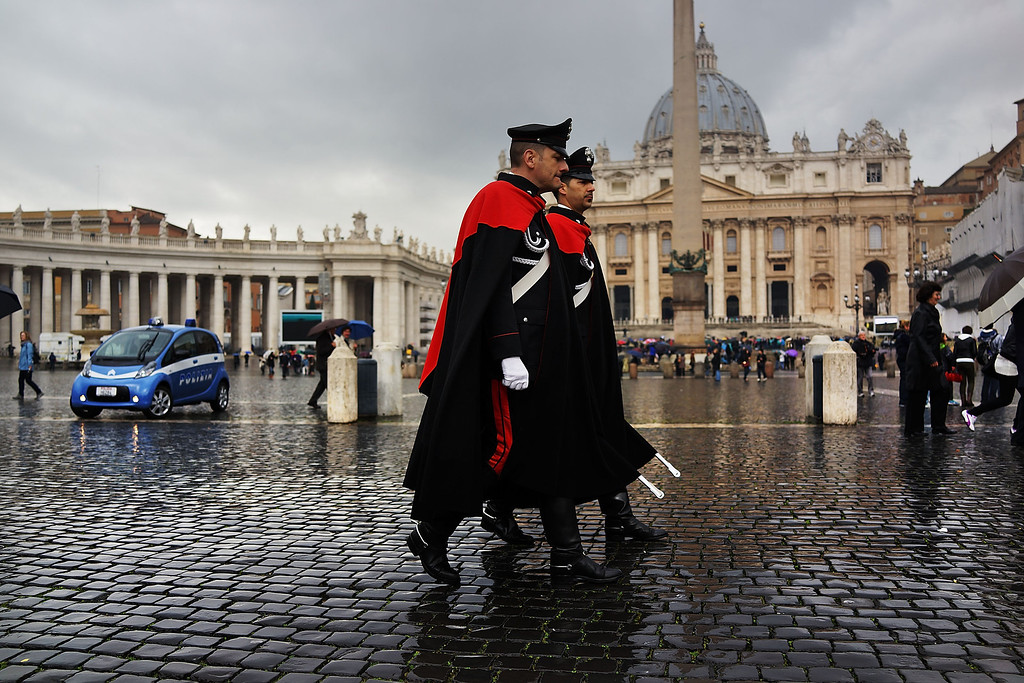 . Italian guards walk in St. Peter\'s Square as poeple wait for smoke to emanate from the chimney on the roof of the Sistine Chapel which will indicate whether or not the College of Cardinals have elected a new Pope on March 13, 2013 in Vatican City, Vatican.  (Photo by Spencer Platt/Getty Images)