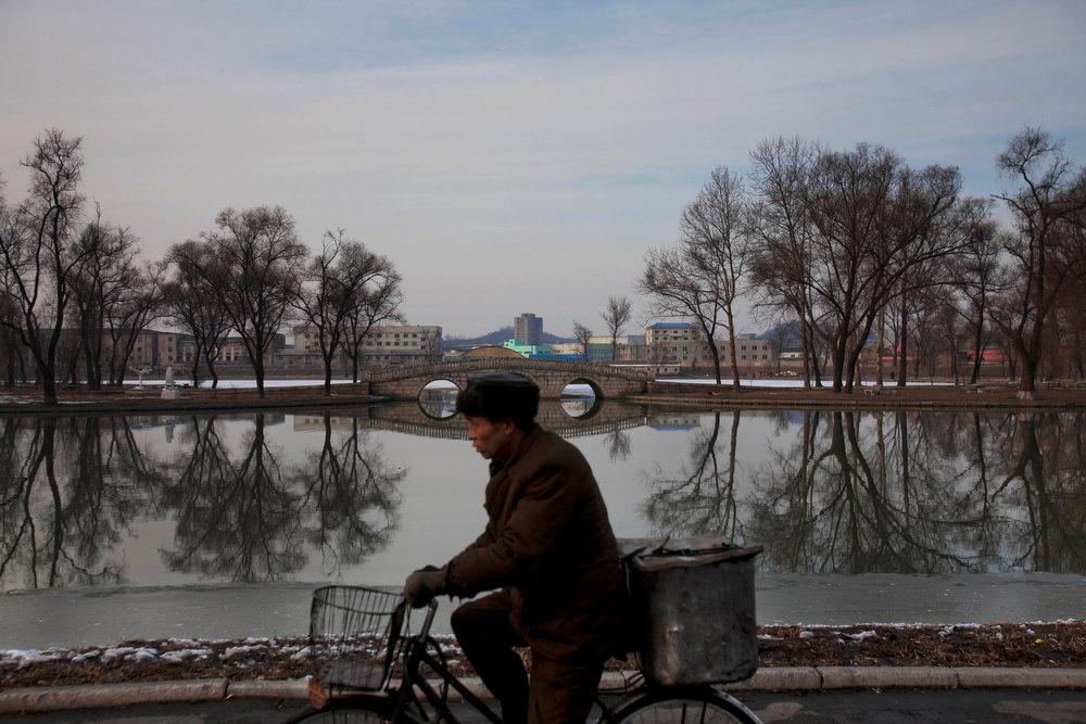Description of . A North Korean man rides a bike along the banks of the Pothong River in Pyongyang on Sunday, Feb. 12, 2012.  (AP Photo/David Guttenfelder)