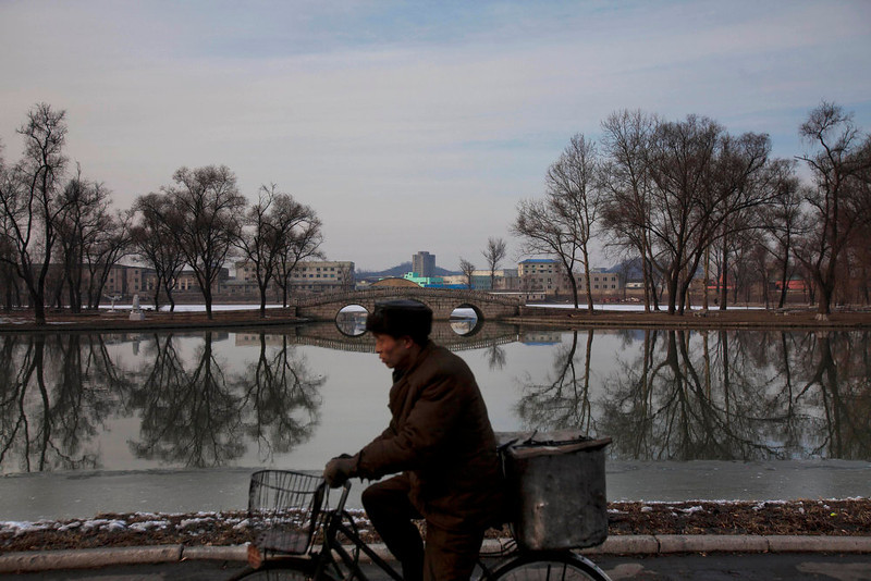 . A North Korean man rides a bike along the banks of the Pothong River in Pyongyang on Sunday, Feb. 12, 2012.  (AP Photo/David Guttenfelder)