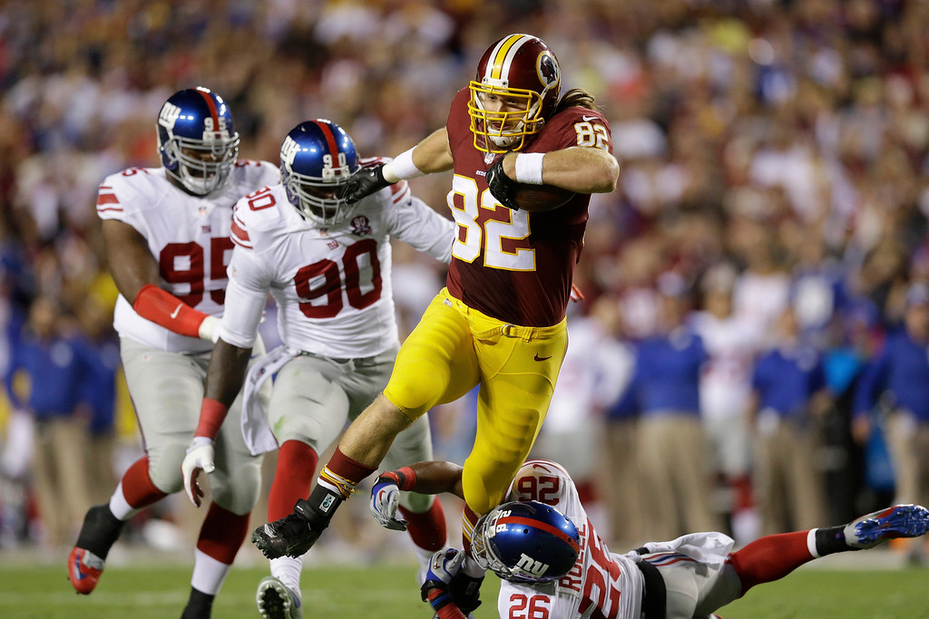 . Washington Redskins tight end Logan Paulsen (82) carries the ball under pressure from New York Giants defensive tackle Johnathan Hankins (95), defensive end Jason Pierre-Paul (90) and strong safety Antrel Rolle (26) during the first half of an NFL football game in Landover, Md., Thursday, Sept. 25, 2014. (AP Photo/Patrick Semansky)