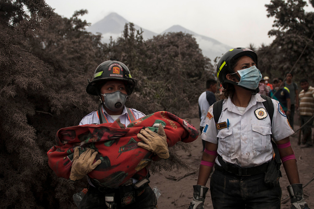 ". A firefighter carries the body of a child recovered near the Volcan de Fuego, or ""Volcano of Fire,\"" in Escuintla, Guatemala, Monday, June 4, 2018. A fiery volcanic eruption in south-central Guatemala sent lava flowing into rural communities killing dozens. (AP Photo/Oliver de Ros)"