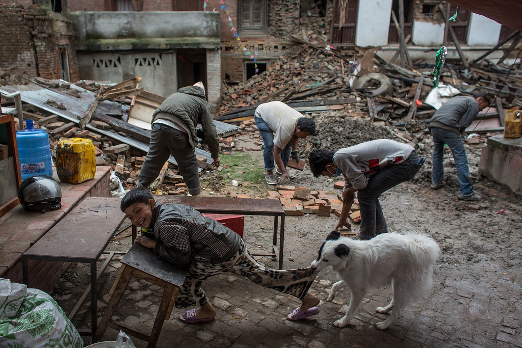 . A boy plays with a dog as family members clean rubble from the front of their home in Shanku on April 30, 2015 in Kathmandu, Nepal. A major 7.8 earthquake hit Kathmandu mid-day on Saturday, and was followed by multiple aftershocks that triggered avalanches on Mt. Everest that buried mountain climbers in their base camps. Many houses, buildings and temples in the capital were destroyed during the earthquake, leaving over 5500 dead and many more trapped under the debris as emergency rescue workers attempt to clear debris and find survivors. Regular aftershocks have hampered recovery missions as locals, officials and aid workers attempt to recover bodies from the rubble.  (Photo by Chris McGrath/Getty Images)